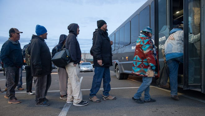 Commuters board a Navajo Transit System bus on Wednesday in a Walmart parking lot at 1400 W. Main Street in Farmington.