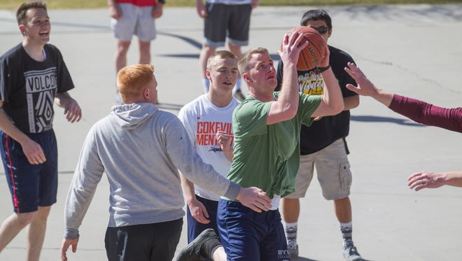 Elder Garett Rumsey, drives to the hoop on Monday during a pick-up game with fellow missionaries from the Church of Jesus Christ of Latter-Day Saints at Brookside Park in Farmington.
