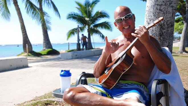 "Kent Terada shows the shaka or ""hang loose"" sign while sitting at Ala Moana Beach Park in Honolulu."