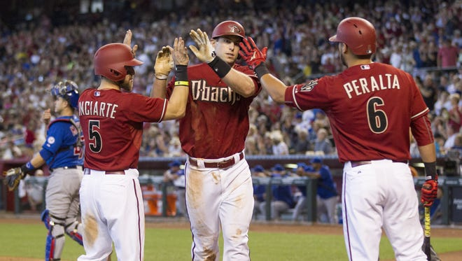 Arizona Diamondbacks' Paul Goldschmidt (center) in congratulated by teammates Ender Inciarte and David Peralta after hitting a two-run home run against the Chicago Cubs during the third inning at Chase Field May 24, 2015.