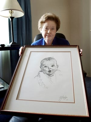 In this Feb. 4, 2004, file photo, Ann Taylor Cook, poses at her Tampa, Fla., home with a copy of her photo that is used on all Gerber baby food products. Gerber says Cook turned 90 on Sunday, Nov. 20, 2016.