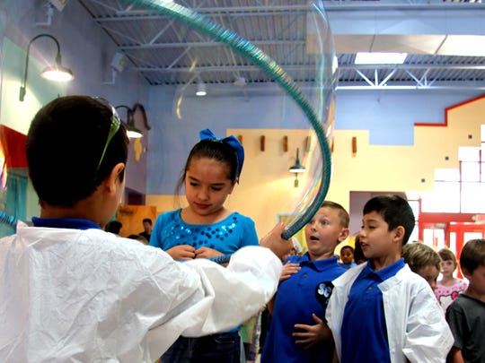 Monterrey Elementary School Sci Squad members envelop a girl from the Early Childhood Education Center in a giant bubble during the school's annual Science Day.
