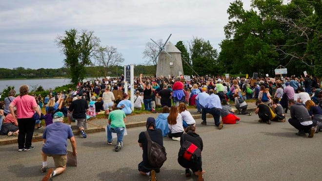 Protesters kneel in silence at Jonathan Young Windmill Friday in Orleans, in support of Black Lives Matter and in memory of George Floyd.