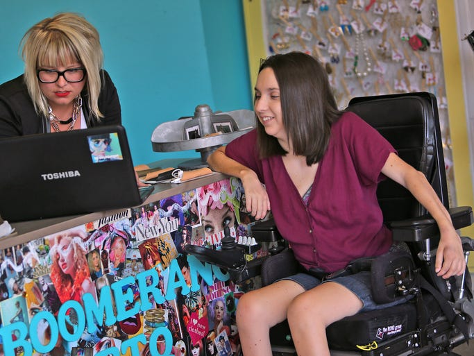Felicia Kiesel (left) looks at marketing tools with Emily Hunt on May 28, 2014, at Kiesel's shop, Boomerang BTQ in Downtown Indianapolis. Hunt was injured at age 4 in August 1996 in an accident at Old Indiana Family Fun-n-Water Park near Thorntown, Ind. She was left with a spinal cord injury. Her grandmother, Nancy Jones, was killed.