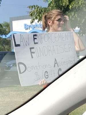 An unknown woman and a group of children stood on Grand River Avenue Wednesday morning seeking donations for law enforcement. (The photo was taken while the driver was stopped at a red light.)