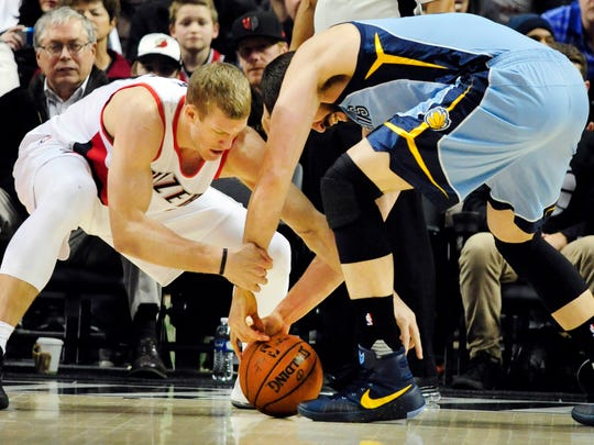 Portland Trail Blazers center Mason Plumlee, left, and Memphis Grizzlies center Marc Gasol, right, go after a loose ball during the first half of an NBA basketball game in Portland, Monday, Jan. 4, 2016.