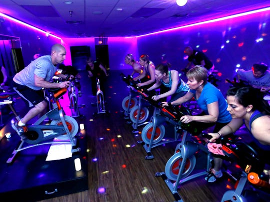 In a studio awash in multi-colored lighting and music, spinners pedal hard during a class at Cycle Down Dawg in West Des Moines.  Co-owner Judd Hardcastle, left, instructs the group.