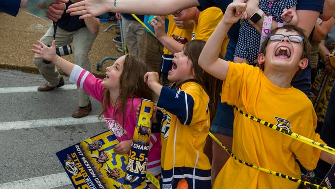 Jackson Polumbo, 8, yells in excitement after high-fiving the Nashville Predators' Mike Fisher at the Nashville International Airport in Nashville, Tenn., before the team travels to Pittsburgh for the beginning of the Stanley Cup Final Saturday, May 27, 2017.