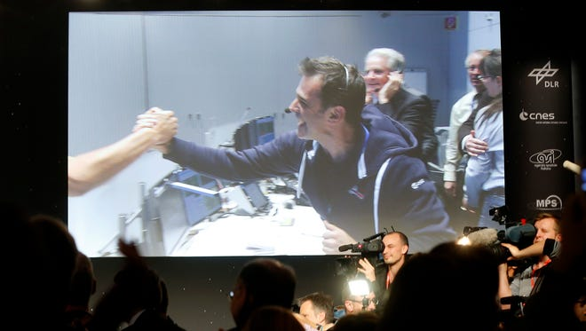 Celebrating scientists in the main control room appear on a video screen at the European Space Agency after the first unmanned spacecraft Philae landed on a comet called 67P/Churyumov-Gerasimenko, in  Darmstadt, Germany, Wednesday, Nov. 12, 2014. Europe's Rosetta space probe was launched in 2004 with the aim of studying the comet and learning more about the origins of the universe.