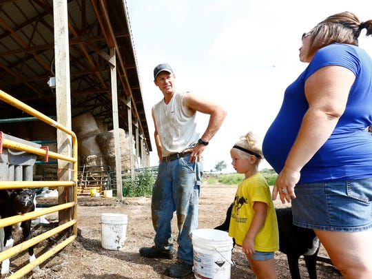 Gary Stankowski, left, his daughter Ella, and wife Holly, all of Mosinee, wait while their calves drink water Wednesday at their dairy farm, Gary's Dairy.