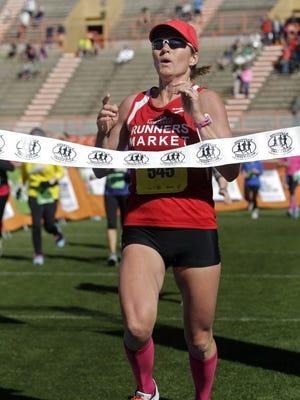 Ladies marathon winner, Gina Rouse, crosses the finish line in Neyland Stadium during the Covenant Health Knoxville Marathon Sunday, April 3, 2016.