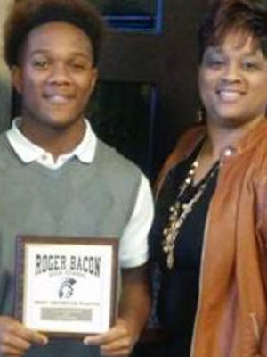 Gregory Thompson Jr. accepts an Outstanding Player of the Year junior varsity football award with his mother Dionne Partee during his freshman year in 2015 at Roger Bacon High School.