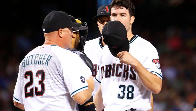 Arizona Diamondbacks pitching coach Mike Butcher (left) talks with pitcher Robbie Ray (38) during the third inning of a baseball game against the Chicago Cubs, Friday, April 8, 2016, in Phoenix.