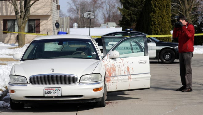 Sgt.Chad Riddle of the Appleton Police Department Crime Scene Unit photographs a car that police said had what appeared to be blood on it at the corner of E. Bradford Ave. and N. Union St. Thursday in Appleton.
