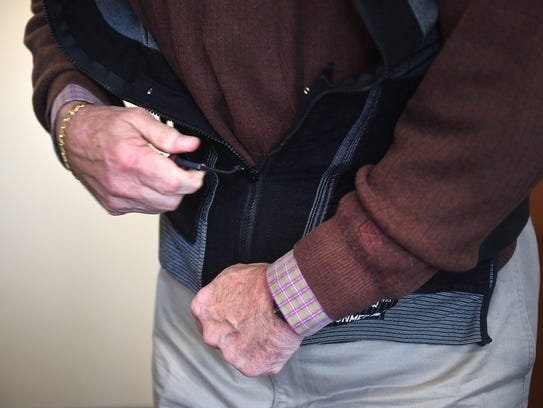 Ted Thoms demonstrates how his back brace helps his