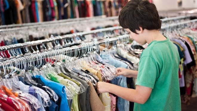 Child shopping for clothes in a thrift store
