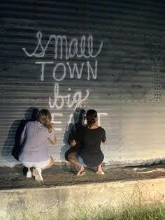 """Madison Kesler, left, and Kyndall Forshee spray paint """"small town big heart"""" on the silo near downtown Prosper in June. The pair originally painted the phrase, which has become a sort of unofficial slogan for the town, on the structure in 2014. The spot has served as a backdrop for countless family and senior photo sessions over the years."""