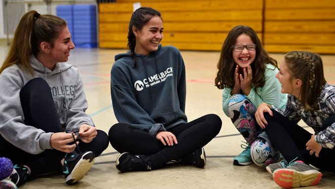 From left, Megan Lutz, 17, and Madison Scopano, 16, both from Manchester Township, spend time with Stella Friedah, 10, and Kyla Myers, 10, at a recent Girls on the Run practice. Megan and Madison are both juniors at Central York High School. This fall, they're volunteering as junior coaches for the Trimmer Elementary School Girls on the Run team in West Manchester Township.