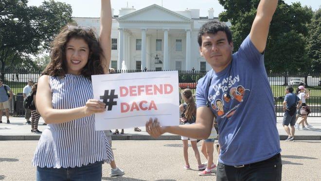 Los jóvenes Claudia Quiñonez (izqda.) y Gerson Quinteros (dcha.) participan en una protesta a las puertas de la Casa Blanca, en Washington, DC,