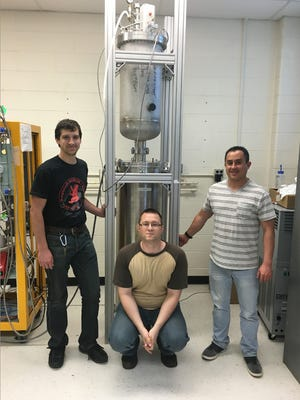 NMSU assistant physics professor Robert Cooper, center, with graduate student Hector Moreno, right, and NMSU undergraduate student Michael Kaemingk shown with a detector for tests at Indiana University, Bloomington. Cooper and Moreno are part of the COHERENT collaborative and among the authors of a recent paper in the journal Science.