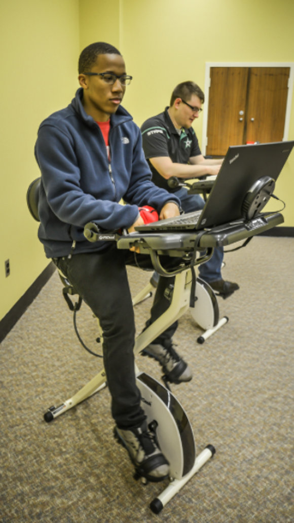 Troy University students Jalen Bivens and William McCarthy use exercise study desks inside library. (Photo by Kevin Glackmeyer)