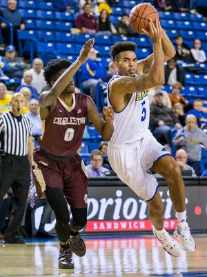 Delaware's Eric Carter cuts to the basket past Charleston's Chevez Goodwin (left) in the second half of a game last season.