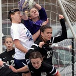 Loyola's Madeline Bodden tries to head the ball past Lakeshore goalie Martha Santos and a host of Lady Titan defenders during their Division II semifinal state playoff game.