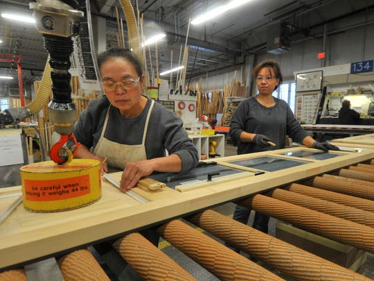 Workers Ger Chang, left, and Mai Her, both of Wausau, assemble a window panel at Kolbe & Kolbe Millwork Company in Wausau.