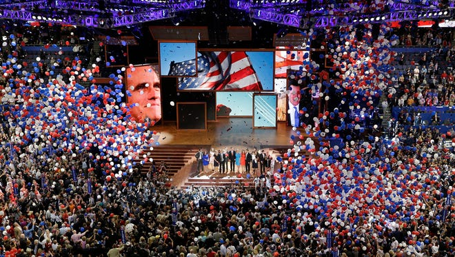 In this Aug. 30, 2012, file photo, Republican presidential nominee Mitt Romney and vice presidential nominee Paul Ryan are joined on the stage by their families at the end of the Republican National Convention in Tampa, Fla.