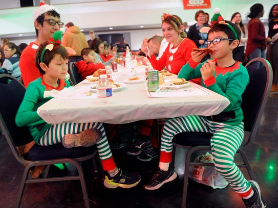 Eight-year-old Gabriel Enriquez, left, Matthew Melendez, 6, eat with their parents Krystal Neves and Christopher Deleon during Tuesday's Feast of Sharing at the Abilene Convention Center. Diners queued up for the free holiday meal, the line snaking through the convention center lobby, then outside and into the north side courtyard.