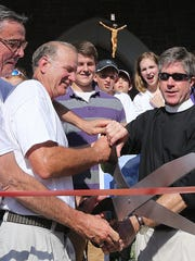 Father Eric Dudley of the St. Peter's Anglican Church does the ceremonial ribbon cutting in 2014.