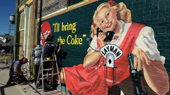Mural artist Michael Cooper and his crew paint a new 1930s retro Coca Cola mural on the side of the Historic Layman Drug Co. building in Chestnut Hill. Restoration of Layman Drug Company building is in progress and  will become a commercial recording space when finished.