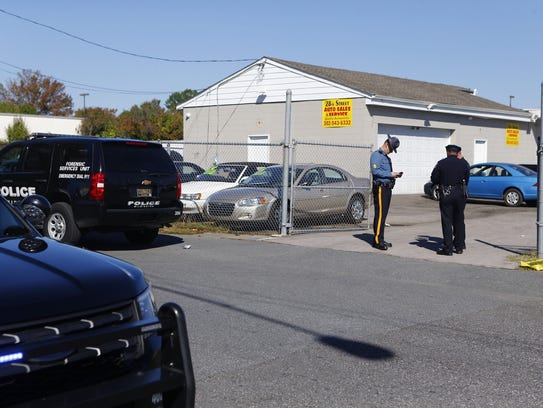 Police investigate the scene of the shooting at 28th Street Auto Sales and Services on the corner of E 28th and Northeast Boulevard in 2017.