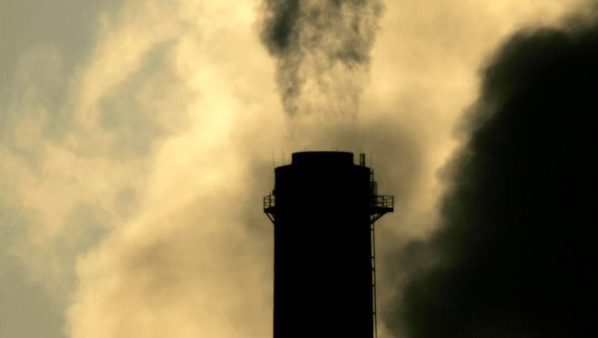 Vapors spew from the smokestack at Sunflower Electric Cooperative's coal-fired power plant in Holcomb, Kan., in February 2007. Eight out of 10 Americans say the climate is changing, according to a new poll.