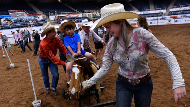 Robbyn Wells of Hereford steers Frankie Pyron of Anson around the Taylor County Coliseum floor on a horse-shaped cart Wednesday. The annual break in the Texas High School Rodeo Association's state finals pairs rodeo contestants and children with special needs for an afternoon of rodeo fun.