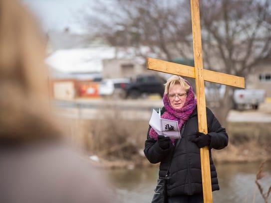 Jennifer Obdzeijewski holds the cross while she leads