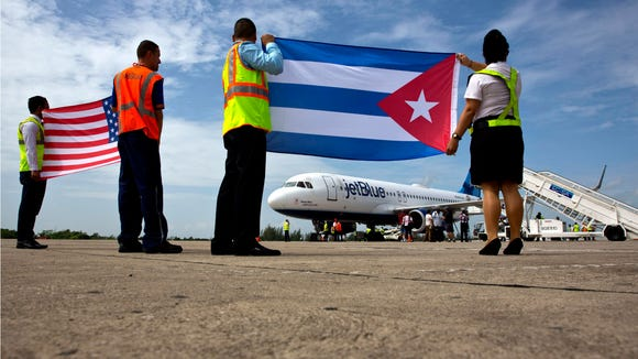 Airport workers receive the JetBlue flight 387 holding