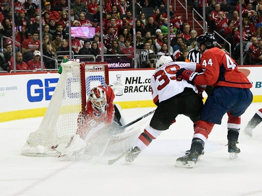 Apr 7, 2018; Washington, DC, USA; Washington Capitals goaltender Braden Holtby (70) saves New Jersey Devils left wing Brian Gibbons (39) shots as defenseman Brooks Orpik (44) defends during the second period at Capital One Arena.
