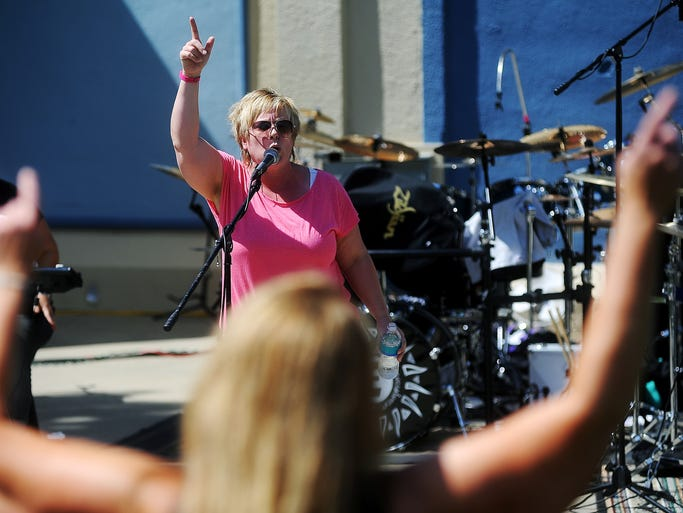 Cara Pliska, with the band Sugardaddy, performs as Amy Ellsworth, singer of Jukebox Zeroes, dances during the 14th annual Jam Against Hunger concert to benefit Feeding South Dakota on Sunday, Aug. 24, 2014, at Terrace Park in Sioux Falls, S.D. Last year, Feeding South Dakota received more than 16-tons of food from the free benefit concert, and this year they are hoping to receive at least 17-tons, Feeding South Dakota executive director, Matt Gassen said.