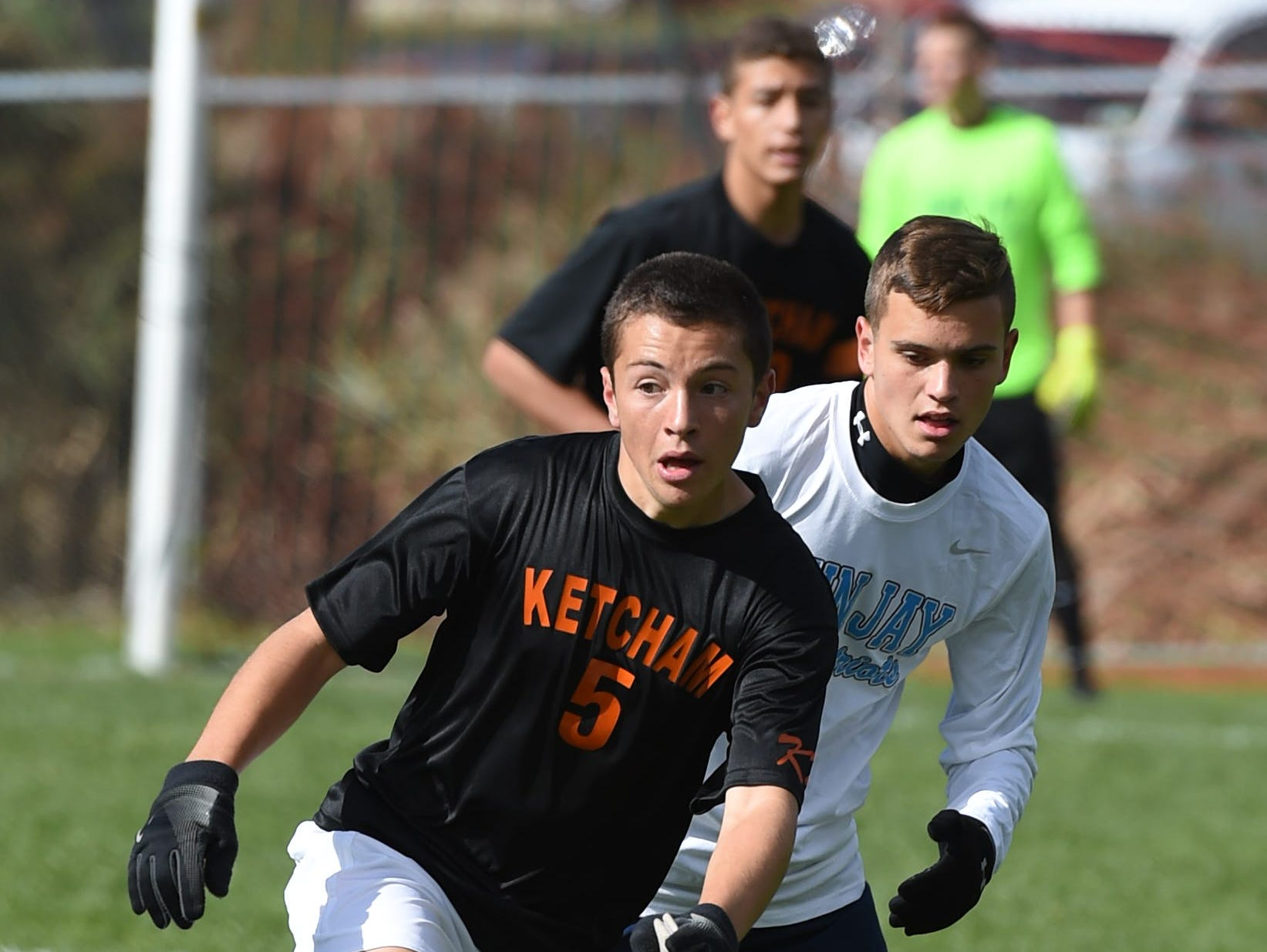 Ketcham's Eddie May looks for a teammate to pass the ball to as John Jay's Mike Ciardullo covers him during Saturday's game in Wappingers Falls.