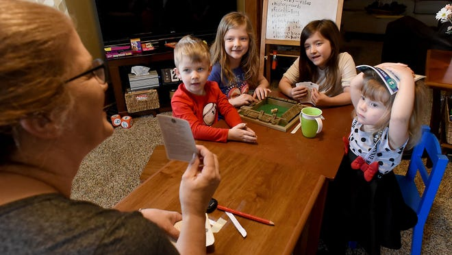 Tammy Massingill holds up flash cards for her grandchildren, who attend Triumph Academy, during the K-12 school closures during the 2019-20 school year. This year, the school is offering a hybrid learning option and a 100% virtual option. School begins Sept. 8.