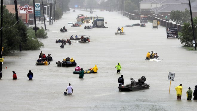 Rescue boats fill a flooded street as flood victims are evacuated as floodwaters from Tropical Storm Harvey rise Monday, Aug. 28, 2017, in Houston.