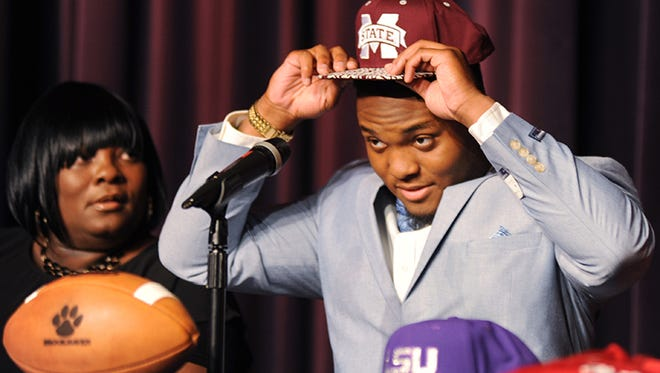 Tina Henderson, left, looks on as her son, Brookhaven High School linebacker Leo Lewis, dons a Mississippi State cap to announce decision to sign with the Bulldogs during an event at the school Wednesday morning.