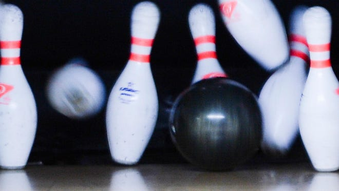 Bowling pins fall during a bowling tournament.