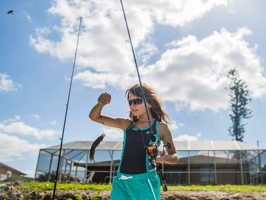 Brianna Wallace, 11, reels up a Mayan cichlid she caught