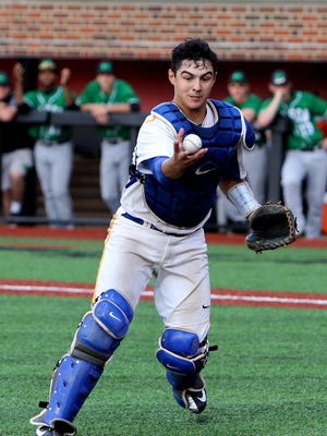 Moeller catcher Bailey Montoya fields a ball against Mason in the regional championship game at the University of Cincinnati.