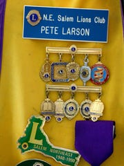 Various Lions Club pins on the vest of 100-year-old