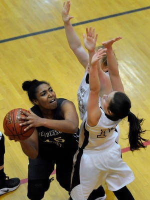 Henderson County's Alisha Owen, left, drives into the lane while Webster County's Jessica Winders and Jamie Winstead defend in the first half of Saturday's Second Region championship game.