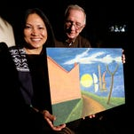 In this Jan. 12, 2016 photo, Erika Colligan poses with former Air Force instructor, retired Col. Billy Mobley as she holds a painting made by her father in San Diego. After three decades searching for her father's artwork - paintings the South Vietnam pilot made for the U.S. Air Force aviators who trained him during the Vietnam war, Colligan recently found one. The painting gave her the first tangible sliver of the father she never got the chance to know. (AP Photo/Gregory Bull)