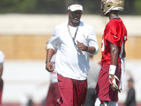 FSU Head Coach Willie Taggart works with his quarterbacks during their opening practice for fall camp at the Al Dunlap Training Facility Monday, Aug. 6, 2018.